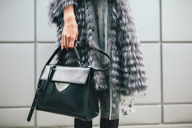 close-up-accessories-details-stylish-woman-walking-city-warm-fur-coat-winter-season-cold-weather-holding-leather-bag-street-fashion-trend_285396-4704