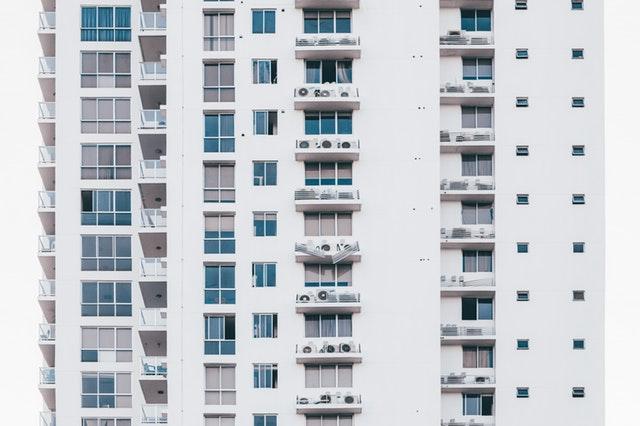 Biela fasáda panelákového domu s množstvom balkónov