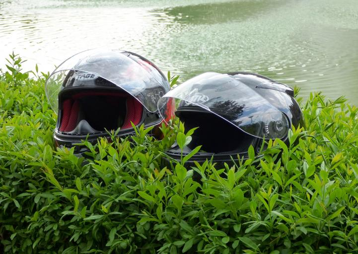 Dve čierne prilby na motorku položené vo vysokej tráve