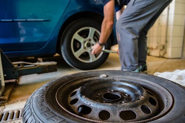 Človek odmontúva pneumatiky z automobilu