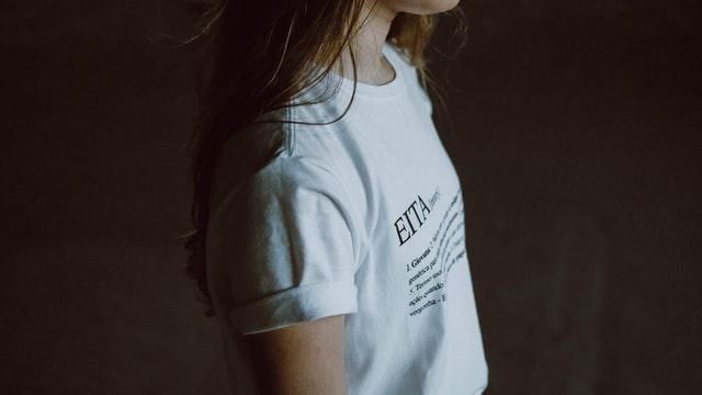Žena v bielom voľnom tričku s čiernym textom