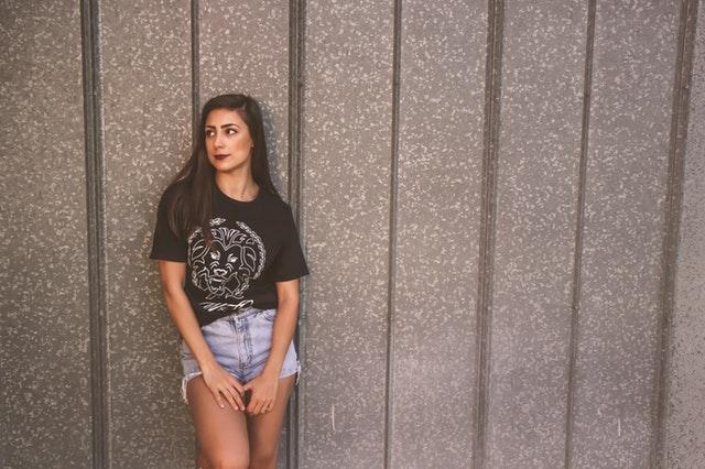Žena v krátkych džínsoch a čiernom veľkom tričku stojí pri sivej stene