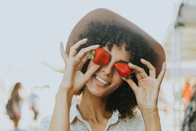 Usmiata žena v klobúku drží pred očami jahody