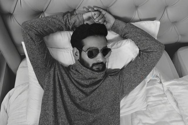 Muž v mikine a slnečných okuliaroch leží v posteli.jpg