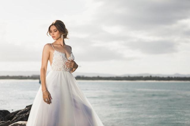 Nevesta v dlhých svadobných šatách stojí na skalách pri jazere.jpg
