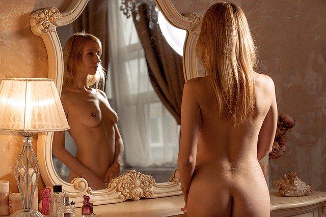 Nahá žena stojí pred zrkadlom