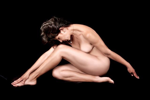 Nahá žena s hnedými vlasmi sedí predklonená